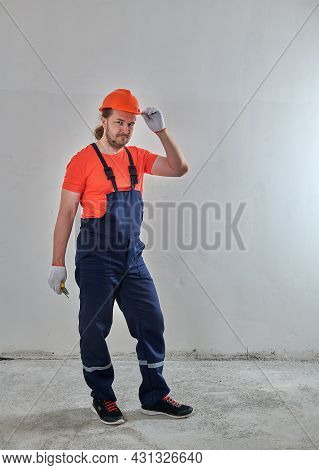 A Rested Repairman Stands Against The Background Of A White Wall