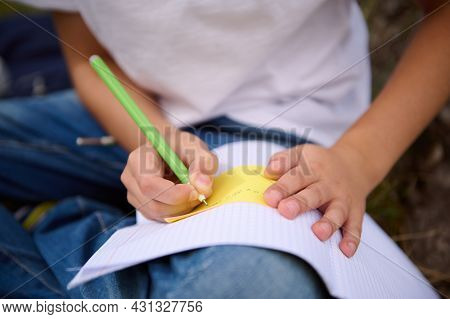 Soft Focus On Schoolboy Hands Holding A Pen And Doing Homework, Writing On Copy Book, Solving Mathem