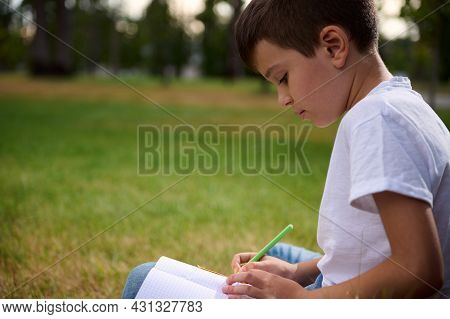 Portrait Of Adorable Elementary Aged Clever Student, Intelligent Schoolboy Doing Homework, Solving M