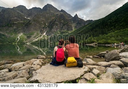 Summer Hike In Mountain. A Young Couple Of Girl And A Man Sitting Relaxing By A Water Lake And Takin