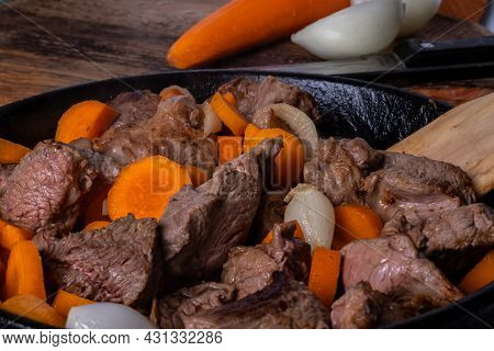 Cooking Process Of Beef Burgeoning In A Frying Pan. Raw Meat, Carrots And Onions. Slow Food Concept.