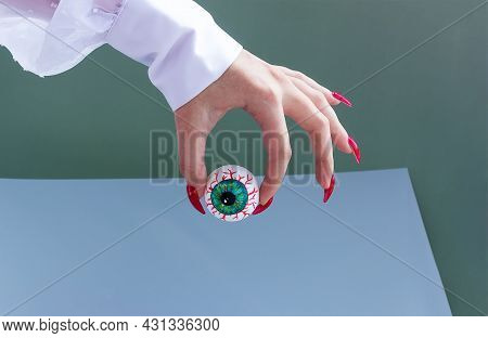 Halloween Creepy Bloody Eye Holds Hand With Long Red Nails