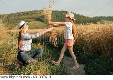 Family Of Farmers, Happy Mother And Daughter In Golden Wheat Field With Hats On Their Heads. The Chi