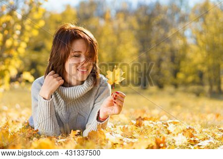 Happy Woman In Autumn Season Relax. Brunette Girl Lying And Smiling At Autumn Golden Leaves In The P