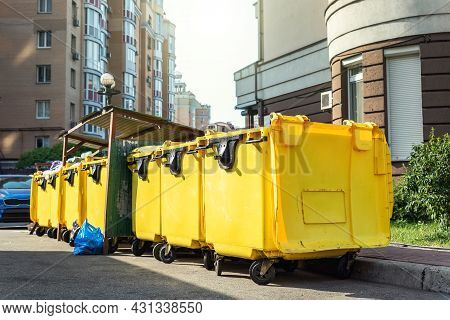 Rows Of Many Big Plastic Yellow Dumpster Cans Full Of Black Plastic Trash Litter Bags Near Residenti