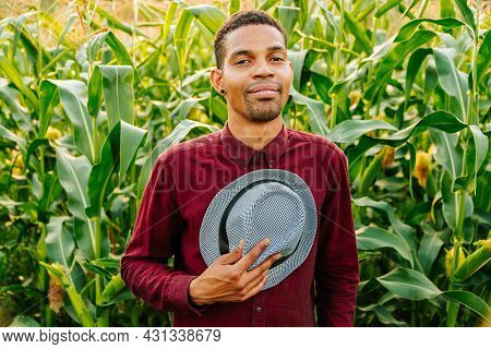 Happy African Farmer Smiling At Camera, Hat In Hand Looking At Camera. Young Black Farmer Man Swings
