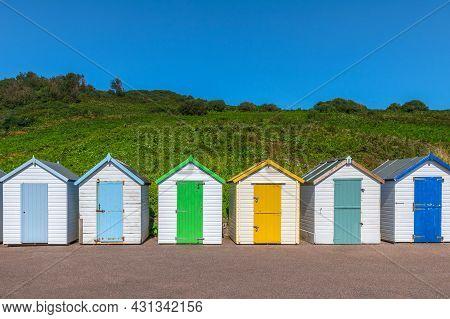 Colourful Beach Houses. Row Of Multicolored Beach Huts Against Blue Sky.