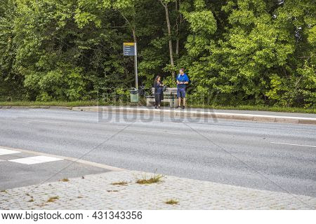 Beautiful View Of Woman And Man Surfing On Mobiles Awaiting Buss On Public Buss Stop. Sweden. Uppsal