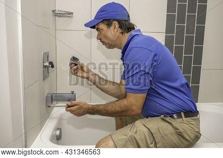Plumber In Bathtub Working On Tub Faucet Handle