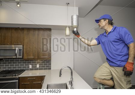 Man Changing A Led Light Bulb In A Kitchen On A Pendant