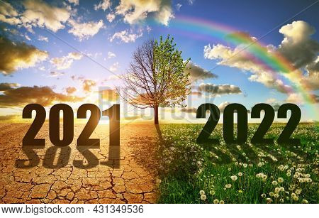 Number 2021 in dry country with cracked soil and 2022 in the green grass. Concept of Happy New Year. Global warming or change climate theme.