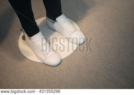 Window Display Of A Male Mannequin Wearing White Shoes.