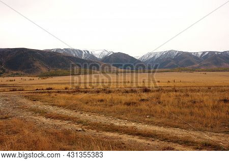 A Field Road Going Through The Autumn Steppe At The Foot Of A Mountain Range With Snow-capped Peaks.