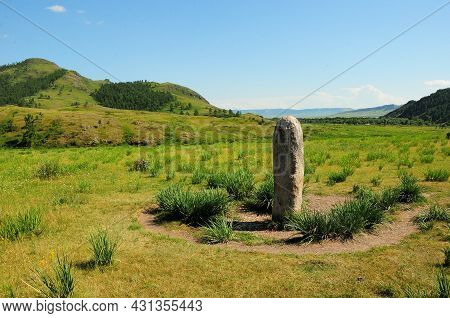 An Ancient Ritual Granite Monolith In The Center Of A Picturesque Valley Surrounded By Mountains.