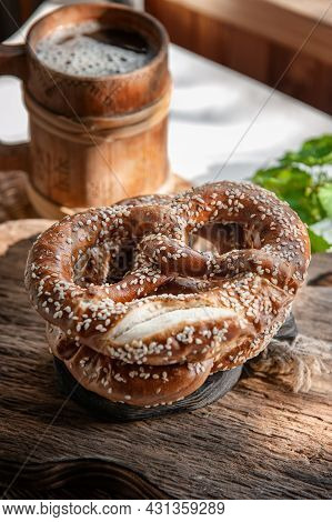 Fresh Pretzel On A Rustic Wooden Table With A Wooden Beer Mug. Rustic Style
