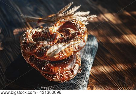 Fresh Pretzel With Wheat On A Rustic Wooden Table. Rustic Style. Copy Of The Space