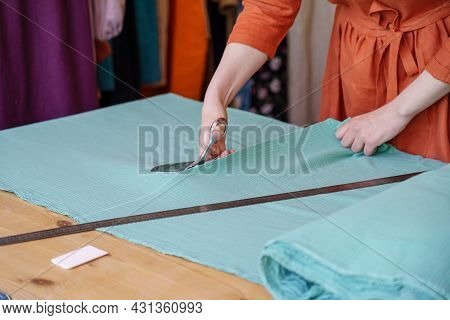 Cropped Shot Of Woman Tailor Cutting Fabric On Table, Working On New Clothing At Workplace In Atelie