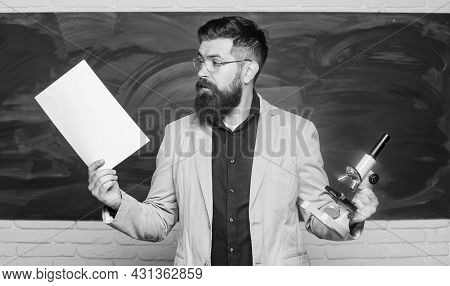 Teacher Bearded Man Hold Documents And Microscope Chalkboard Background. Biology Is His Passion. Dem