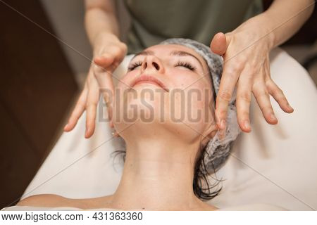Beauty Treatments: Facial Massage In The Treatment Room. A Woman In A Beauty Salon. Young Female Get