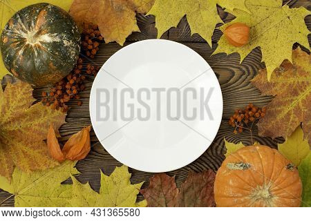 Autumn Table For Thanksgiving Dinner. Top View Of Maple Leaf On A White Empty Plate And Fallen Color