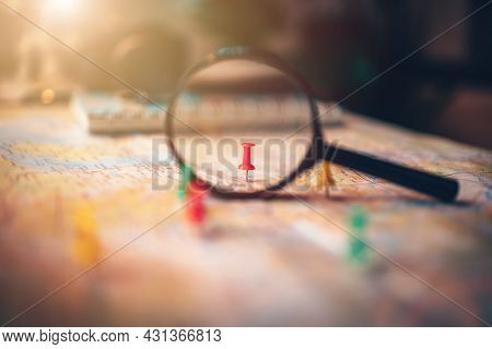 A Magnifying Glass With Pins Pinned On The Map. Pushpin Showing The Location Of A Destination Point