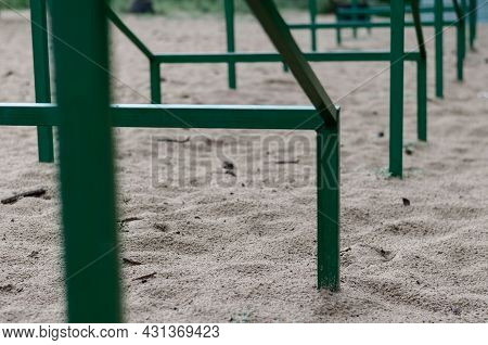 Close-up Of A Recurring Green Metal Structure Set In The Sand In A Receding Perspective. Special Ath