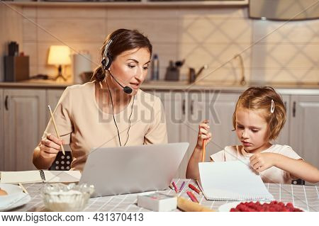 Girl Drawing In Notepad While Mother Working Remotely On Laptop