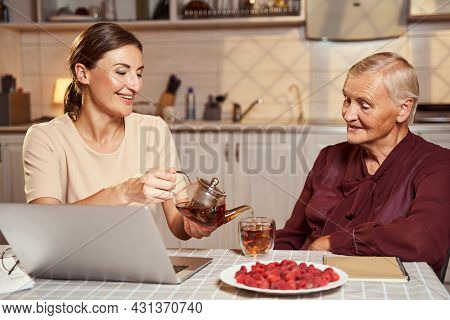 Pleased Female Treating Senior Citizen With Tea