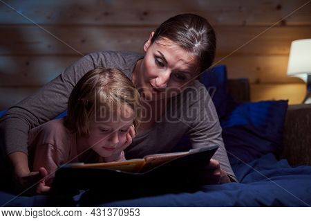Child Lying In Bed And Reading Storybook With Her Mother