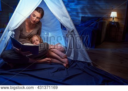 Mother With Storybook Helping Her Daughter To Fall Asleep