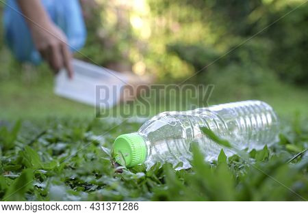 Plastic Bottle With Volunteer At The Background Picking Up Plastic Rubbish. Volunteering And Plastic