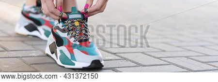 Woman Tying Shoelaces On Sports Sneakers Closeup