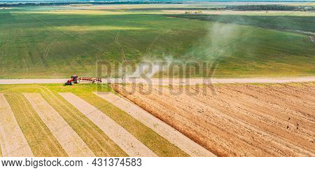 Aerial View. Tractor Plowing Field In Spring Season. Beginning Of Agricultural Spring Season. Cultiv