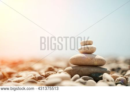 Zen Stones Are Background. A Pyramid Of Pebble Stones Against The Background Of The Sky, Sea And Bea