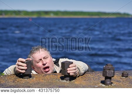 Freak Clings His Hands To The Edge Of The Cliff Above The Water. Emotional Frame Of The Struggle For
