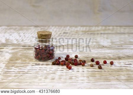 Glass Jar With Red Pepper Corns And Cork On Light Wooden Board Front View