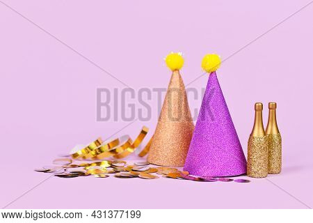 Glittering Party Hat, Small Golden Champagne Bottles And Party Streamers On Violet Background With C