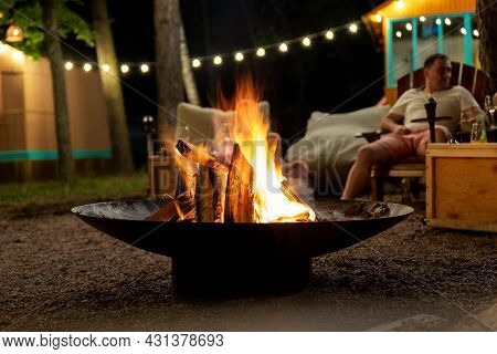 Cast Iron Fire Pit Campfire Place At Forest Beach Camping With Brgiht Burning Flame At Evening Time
