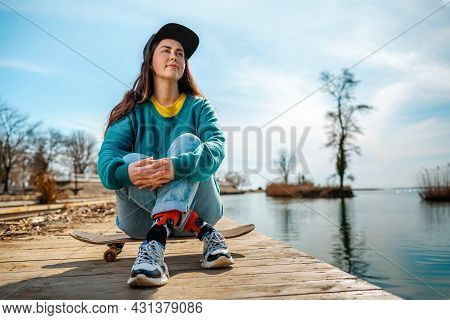 A Young Caucasian Hipster Woman Sits Cross-legged On A Skateboard And Poses. In The Background-the R
