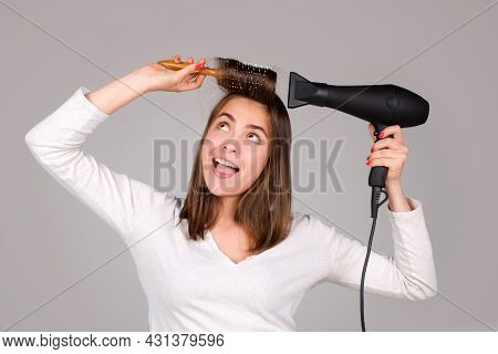 Funny Woman With Hair Dryer. Beautiful Girl With Straight Hair Drying Hair With Professional Hairdry