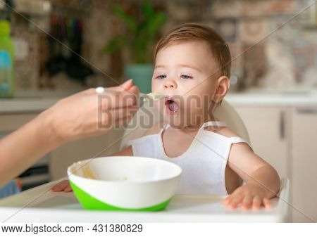 Feeding Child. Cute Baby Eating Food. His Mother Feeds Him With A Spoon. First Lure. Portrait Of A H