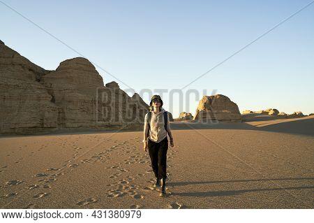 Asian Woman Traveler Backpacker Walking In Desert At Sunset With Yardang Landform In Background