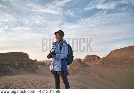 Asian Woman Female Photographer Looking At Landscape In Gobi Desert With Yardang Landforms