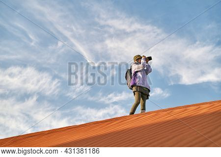 Asian Woman Photographer Standing On Top Of A Sand Dune Taking A Picture