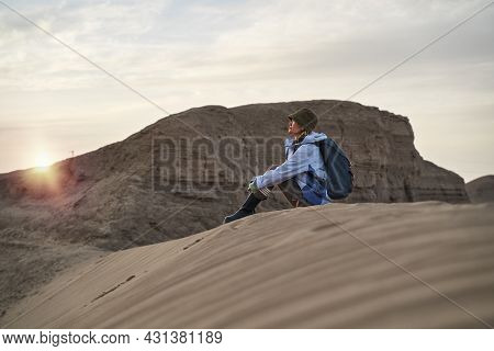 Young Asian Woman Backpacker Sitting On Ground Relaxing Resting Watching Sunset