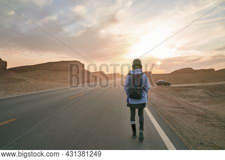 Rear View Of Woman Traveler Walking On Highway In Gobi Desert With Yardang Landforms
