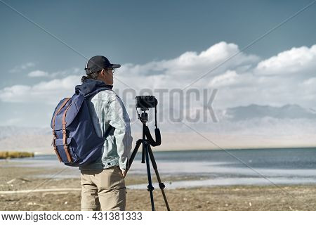 Asian Photographer Standing By A Lake Looking At View Observing