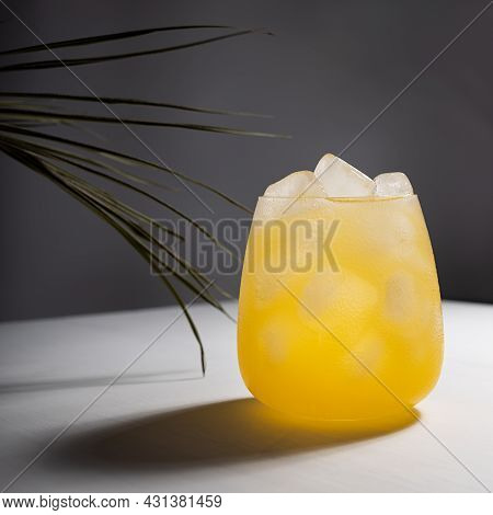 Cold Fresh Summer Orange Cocktail With Vodka, Ice Cubes Shining In Sunlight With Shadows, Green Palm