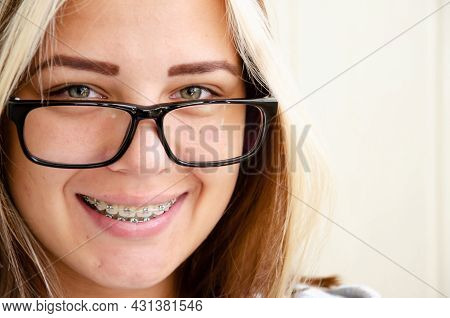 Brunette Teen Girl With Glasses In Dental Braces. Beautiful Caucasian Young Girl With Green Eyes Loo