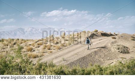 Rear View Of An Asian Man Backpacker Photographer Walking On A Dirt Road Through Gobi Desert